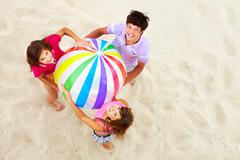 Above angle of happy teenage friends with multi-colored ball looking at camera Stock Photos