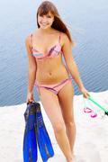 Portrait of teenage girl in bikini carrying scubadiving equipment Stock Photos