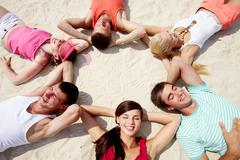 Six friends lying on sand in circle Stock Photos