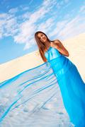 image of female wrapped into blue chiffon looking at camera on sandy beach - stock photo