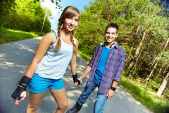 Teen couple skating in park on a sunny summer day Stock Photos