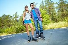Summer portrait of happy teens roller skating in park Stock Photos