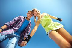 portrait of two cheerful teenagers viewed from below against clear blue sky - stock photo