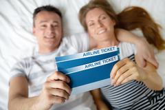 happy young couple lying on bed with air tickets in hands - stock photo