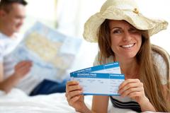 Happy woman in hat showing flight tickets Stock Photos