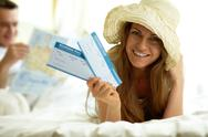 Stock Photo of elegant woman in hat holding flight tickets and looking at camera