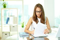 concentrated girl working with document attached to a clipboard - stock photo
