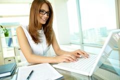 close up of a pretty female businessperson typing with a smile - stock photo