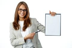 Pretty lady smiling at cam holding a clipboard with an attached blank Stock Photos