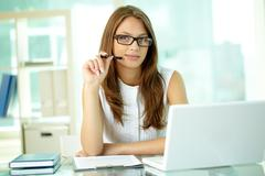 portrait of a positive business woman at her workplace - stock photo