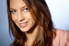 close-up portrait of an attractive brunette glancing teasingly at camera - stock photo