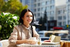 Image of happy female in open air cafe having coffee with cake in urban environm Stock Photos