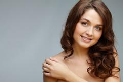 portrait of feminine woman touching her shoulder and looking at camera - stock photo