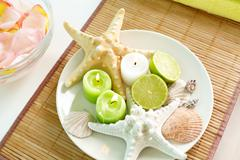 candles, citrus and sea-stars lying on the porcelain plate - stock photo