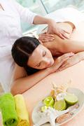 vertical shot of a girl lying on the massage table, massage therapist doing the - stock photo