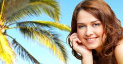 Portrait of a smiling young woman having a trip to a tropical paradise Stock Photos