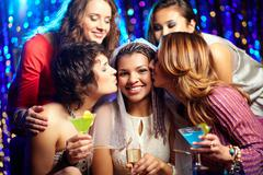 Beautiful female friends congratulating the bride and kissing her Stock Photos