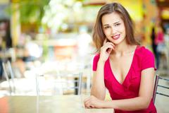 Adorable girl waiting for her friend in a summer cafe Stock Photos