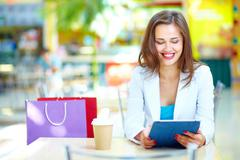 Shopping girl laughing looking at the screen of her portable device Stock Photos