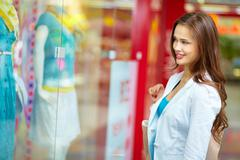 Smiling girl looking at the shop window before entering the store Stock Photos