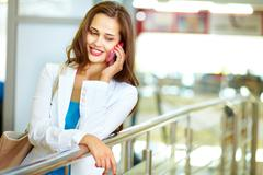 Girl with a pleasant smile speaking over the phone indoors Stock Photos