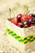 close-up of ripe cherries in small wattled basket - stock photo