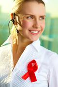 Portrait of smiling woman with headset and red ribbon on blouse Stock Photos
