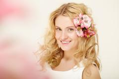 charming blonde with fresh flowers in her hair - stock photo