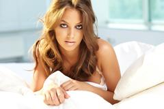 Posh young woman lying in bed and looking at camera Stock Photos