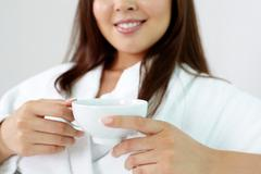 Close-up of young woman holding a cup of aromatic tea Stock Photos
