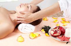 massage therapist helping young woman accumulate energy after a workweek - stock photo