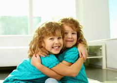 Portrait of cheerful twin sisters hugging and smiling at cam Stock Photos