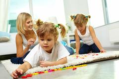 Stock Photo of portrait of cute girl playing with letters with her mother and twin sister on ba