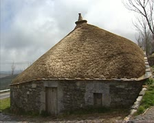 Round stone houses with straw roof - pan O'Cebreiro Stock Footage