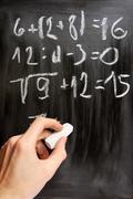 hand writes mathematical equations on black blackboard - stock illustration