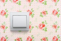 light switch on retro floral wallpaper - stock photo