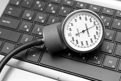 sphygmomanometer on laptop keyboard - stock photo
