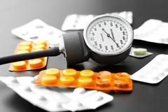 blood pressure meter and pills on the table - stock photo