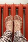 feet with wool socks warming on the radiator - stock photo