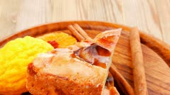 Sweet apple cake with lemon and cinnamon sticks on wooden table Stock Footage