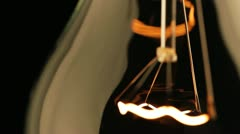 Real light bulb turning on, back lit, close-up - stock footage