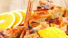Baked food: apple pie on wooden table served with lemon and cinnamon sticks Stock Footage