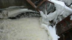 Strong water stream flow splash retro dam ice snow winter Stock Footage