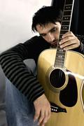 Young man with a guitar Stock Photos