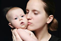 Mother kissing her little baby Stock Photos