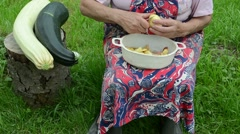 Dish peeled potatoes grass old woman hands shave potato knife Stock Footage