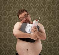 Overweight white male holding scales while resisting temptation Stock Photos