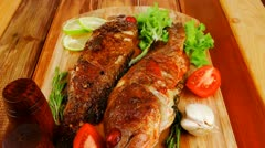 Main portion of two grilled fish served on wooden table with castors Stock Footage