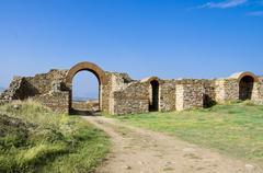 Ancient town ruins and path through arced stone gate Stock Photos