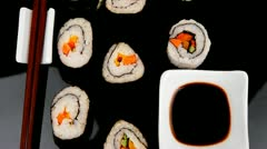 Sushi Maki Roll with Vegetables and Salmon inside . on black plate Stock Footage
